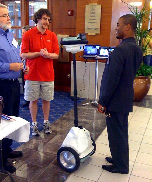 Stephen Wolfram greets a reception guest via an Anybot telepresence robot